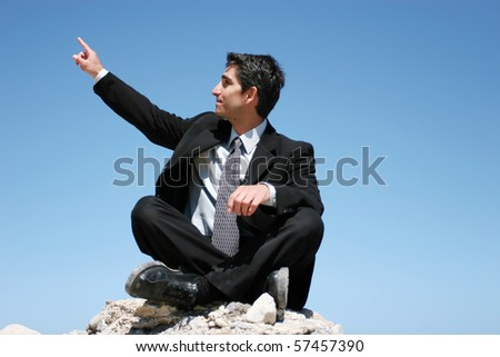 Businessman in black suit sitting on the rocks - stock photo