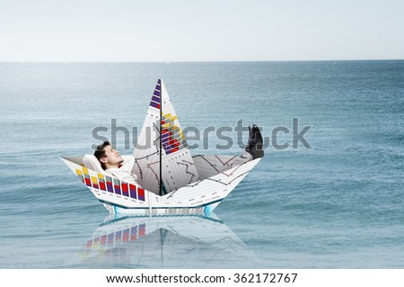 Businessman in boat made of paper - stock photo