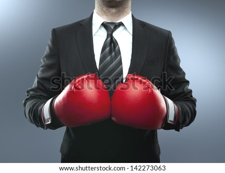 businessman in boxing gloves isolated on blue - stock photo