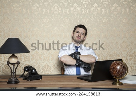businessman in boxing gloves sitting in office - stock photo
