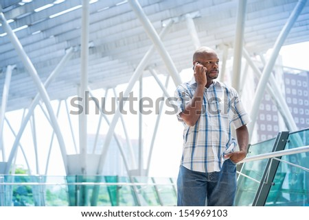 Businessman in casual making a serious phonecall inside - stock photo