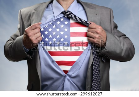 Businessman in classic superhero pose tearing his shirt open to reveal t shirt with the American flag concept for patriotism, freedom and national pride - stock photo