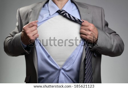 Businessman in classic superman pose tearing his shirt open to reveal t shirt with blank chest for message - stock photo