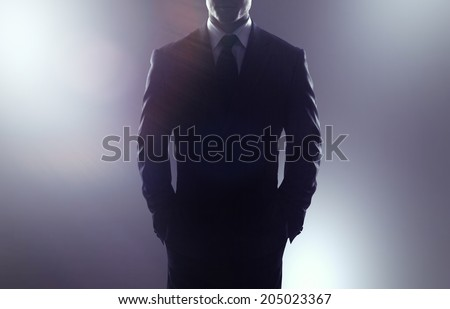 businessman in coat on a gray background - stock photo
