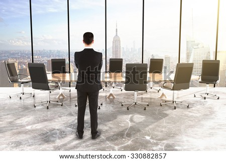 Businessman in conference room with big round table and chairs in the room with concrete floor and city view 3D Render - stock photo