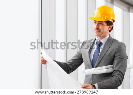 businessman in construction helmet with blueprints - stock photo