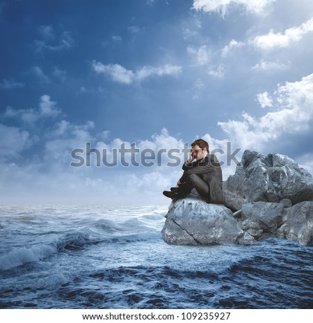 Businessman in crisis on the rocks - stock photo