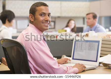 Businessman in cubicle with laptop smiling - stock photo