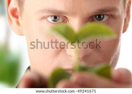 Businessman in dark suit holding small plant in his hands - growth concept - stock photo
