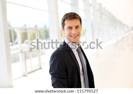 Businessman in dark suit standing in hall - stock photo