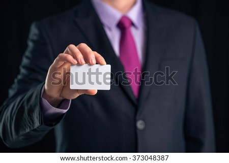 Businessman in elegant suit and with a tie, shows business card with copy space, studio shot - stock photo