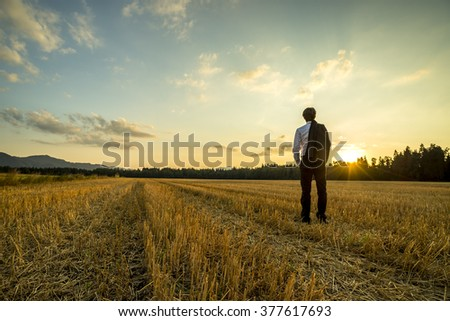 Businessman in elegant suit with his jacket hanging over his shoulder standing in mown wheat field looking into the distance under a majestic evening sky with a setting sun. - stock photo