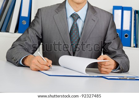 Businessman in elegant suit working with documents sign up contract, holding clipboard, folder with papers, business plan, handwriting, sitting at the desk at office - stock photo