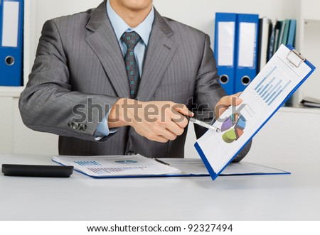 Businessman in elegant suit working with documents sign up contract, holding clipboard, folder with papers, financial business plan, sitting at the desk at office - stock photo