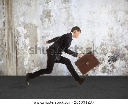 Businessman in formal wear running over grey background - stock photo
