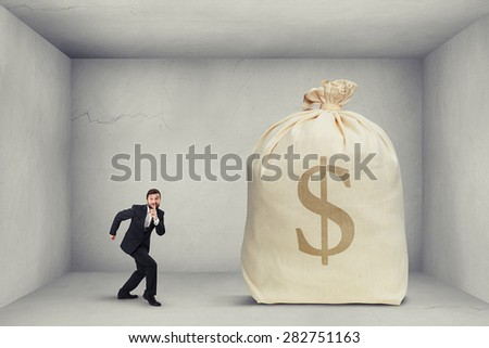 businessman in formal wear showing silent sign and walking on tiptoe to the big bag of money in grey room  - stock photo