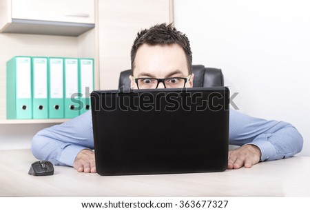 Businessman in front of laptop staring being upset and surprised - stock photo