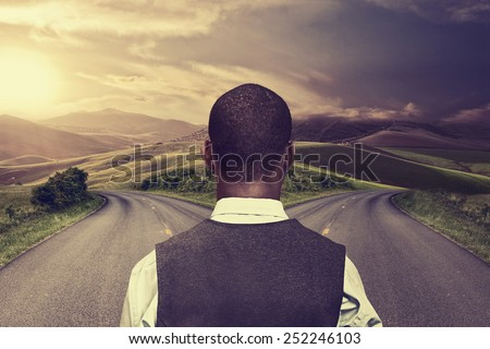 businessman in front of two roads hoping for best taking chance - stock photo