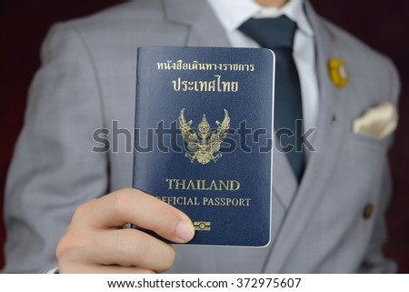 businessman in grey suit showing official passport to travel aboard, business trip - stock photo