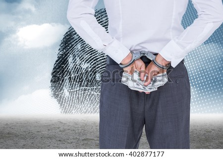 Businessman in handcuffs holding bribe against thumbprint graphic over desert - stock photo
