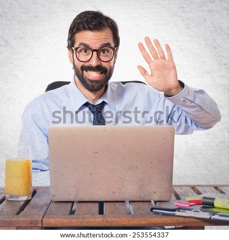 Businessman in his office saluting somebody - stock photo