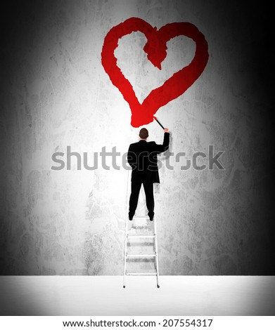 Businessman in love painting a red heart on a grunge wall - stock photo