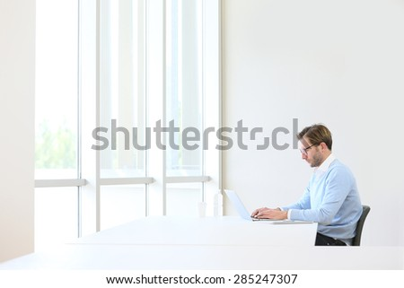 Businessman in modern office working on laptop - stock photo