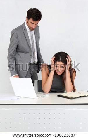Businessman in office harassing young woman - stock photo