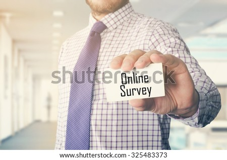 businessman in office showing card with text: Online Survey - stock photo