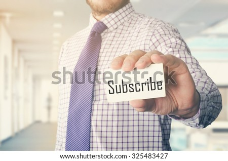 businessman in office showing card with text: Subscribe - stock photo