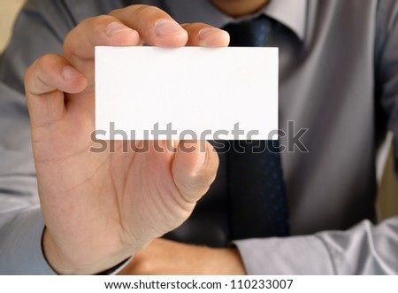 Businessman in office shows the business card in his hand - stock photo