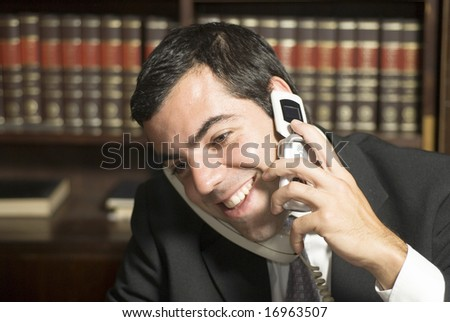 Businessman in office smiling while he talks on phone. Horizontally framed photo. - stock photo