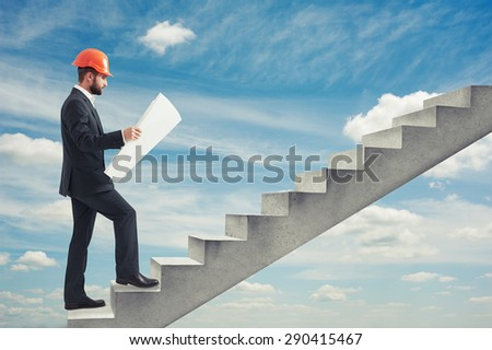 businessman in orange hardhat holding blueprint and following up on concrete stairs over blue sky - stock photo