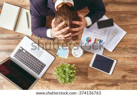 businessman in panic. a young man sits at his Desk and holds his hands on his head. - stock photo