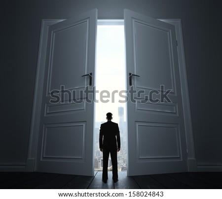 businessman in room with door to city - stock photo