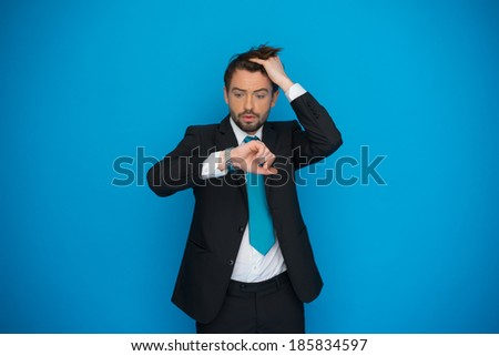 businessman in rush looking at his watch , running late on blue - stock photo
