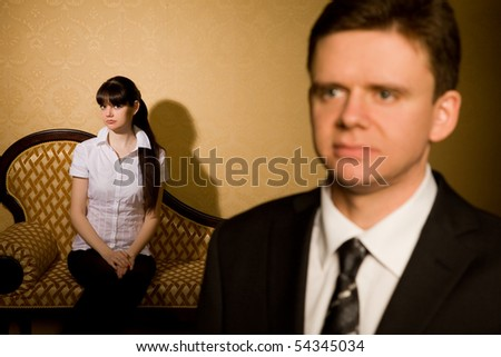 businessman in suit and beautiful young  brunette woman sitting on sofa in room, focus on woman - stock photo