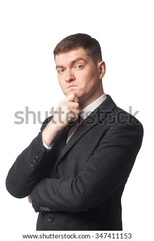 Businessman in suit and black tie with hand on chin on white isolated background - stock photo