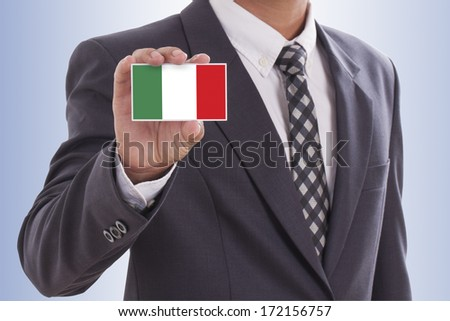 Businessman in suit hand holding a business card with Italy Flag - stock photo