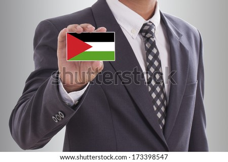 Businessman in suit holding a business card with Palestine flag  - stock photo