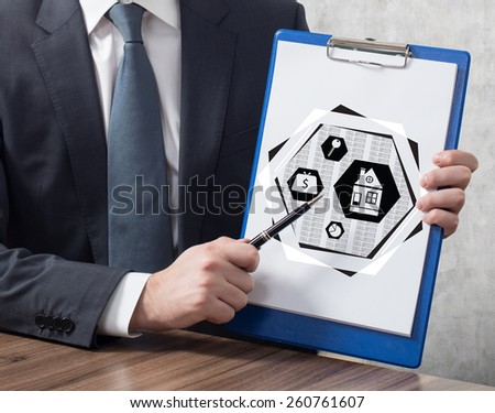 businessman in suit holding clipboard with real estate concept - stock photo