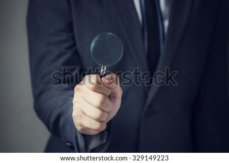 Businessman in suit looking for something using a small magnifier. It indicates many aspects such as looking for opportunities, looking for careers, investigating a crime. monitoring changes. - stock photo