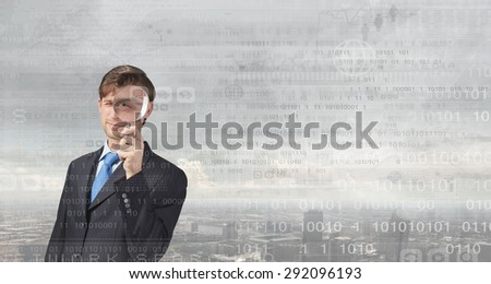 Businessman in suit looking through magnifying glass - stock photo