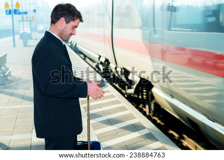 businessman in suit on railroad station waiting for train - stock photo