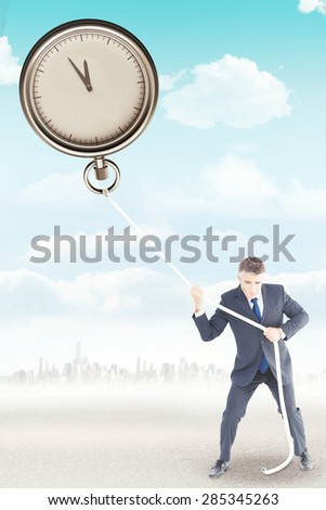 Businessman in suit pulling a rope against city on the horizon - stock photo