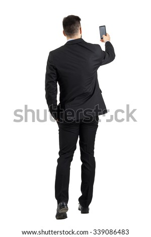 Businessman in suit searching for good phone signal rear view or taking photo. Full body length portrait isolated over white studio background.  - stock photo