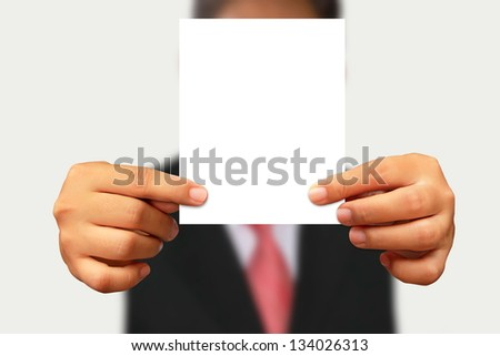Businessman in suit showing blank paper on white background - stock photo