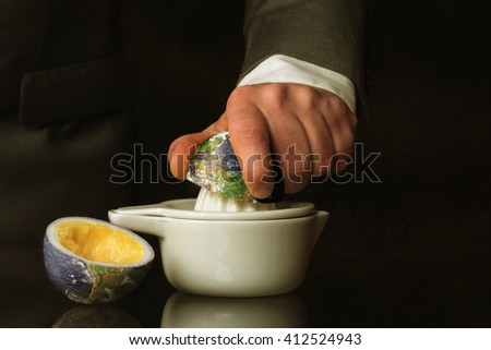 Businessman in suit squeezes the Earth - stock photo