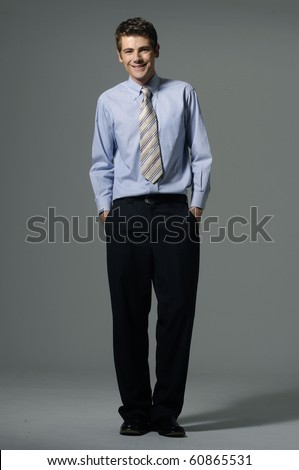Businessman in suit stands with confidence on gray - stock photo