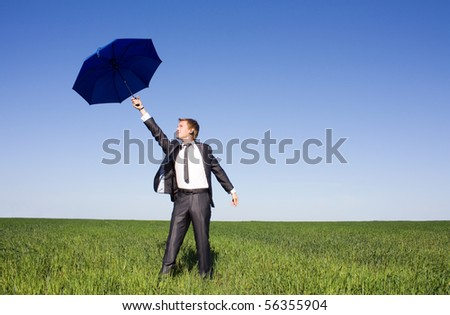 Businessman in the field carries a strong wind - stock photo